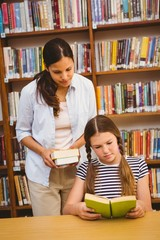 Teacher and girl reading book in library