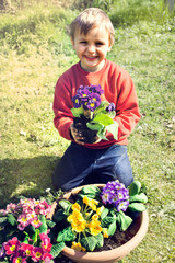 child showing his new pot of flowers in the garden in springo