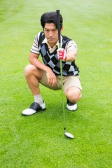 Crouching golfer holding club looking away