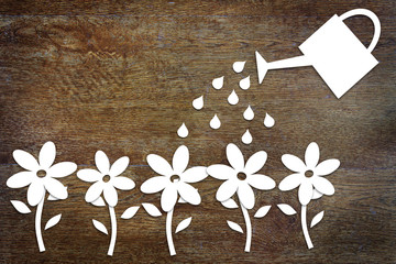 Concept of gardening. Paper flowers and a watering can on wood
