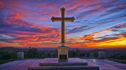 Christian cross on colorful sunset sky, Religion background