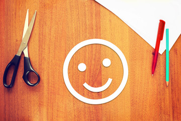 Happy smiley made of paper on the desk. Concept of good emotions
