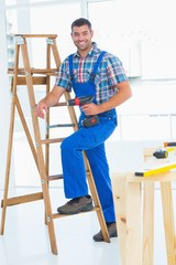 Carpenter with power drill climbing ladder at construction site