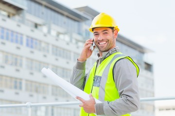 Smiling male architect with blueprints talking on mobile phone