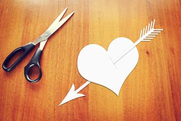 Paper heart pierced by an arrow on the table