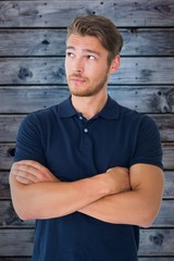 Composite image of handsome young man thinking with arms crossed