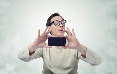 Man in glasses photographed by smartphone