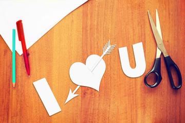 Symbol of love a paper heart pierced by an arrow on the desk