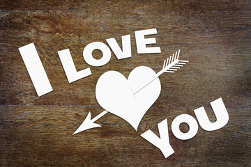 Text I Love You and a paper heart pierced by an arrow