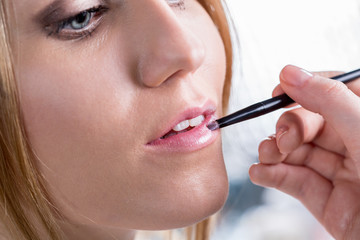 Bride paints lips before wedding