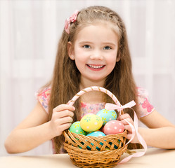 Smiling little girl with basket full of colorful easter eggs