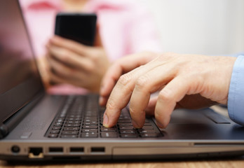 businessman is typing on laptop keyboard with woman in blurred b