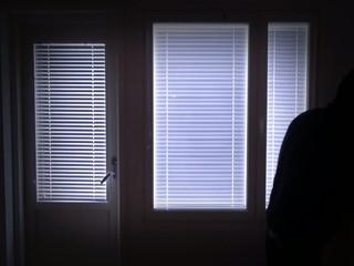 Sneaking burglar with gun and crowbar passing window