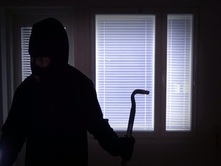 Burglar with crowbar breaking in from back door