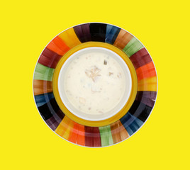 A bowl of clam chowder on a yellow background