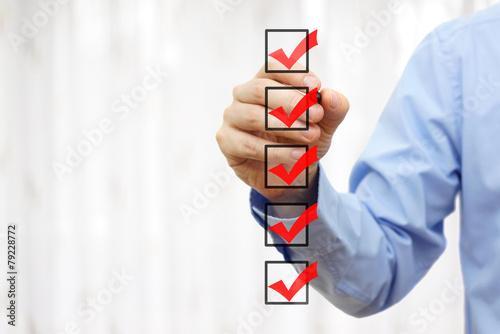 Leinwanddruck Bild businessman checking final  mark on checklist