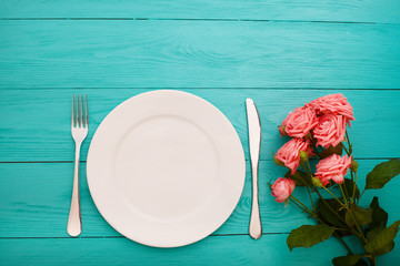 Festive dinner and roses on blue wooden background