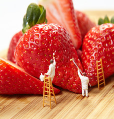 Small figures of painters paint strawberries