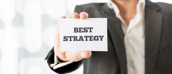 Businessman holding up a card saying Best Strategy