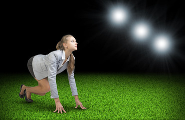 Woman begins to start. Green grass and black sky with rays of