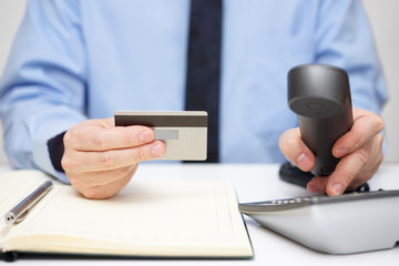 businessman with credit card dialing phone for  support