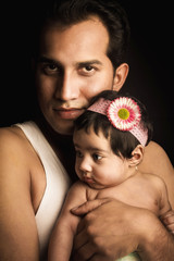 Father posing with infant daughter isolated in black