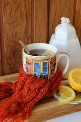 Warming cup of tea, tied with a scarf.