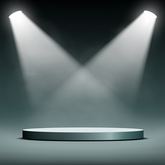 two spotlights illuminate the podium for the presentation