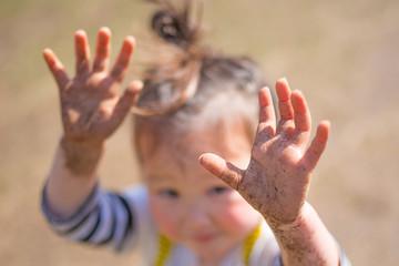 泥だらけになった子供の手