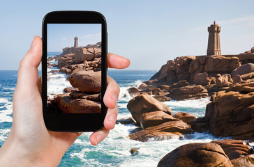 tourist taking photo of Lighthouse in Brittany