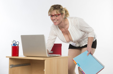 Sexy secretary with plunging neckline working at desk