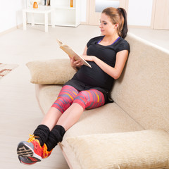 Pregnant woman reading a book at home