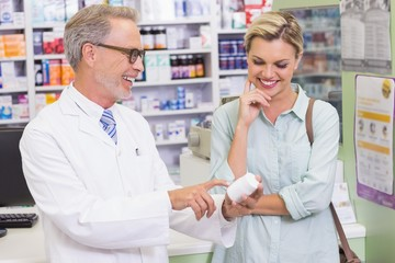 Pharmacist and customer looking at medicine