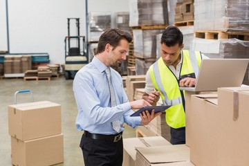 Warehouse worker and manager working together