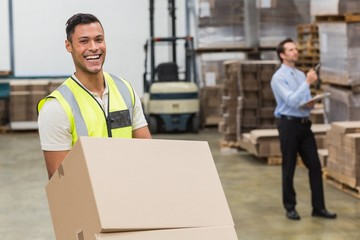 Smiling warehouse worker moving boxes on trolley