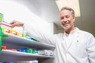 Senior pharmacist taking medicine from shelf