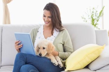 Beautiful woman with dog using digital tablet on sofa