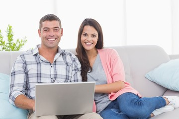 Happy couple with laptop on sofa