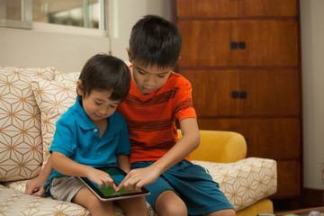 Two young brothers playing with a digital tablet at home