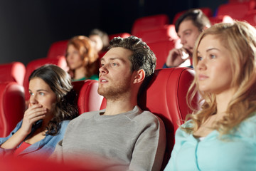 happy friends watching horror movie in theater
