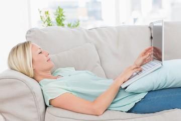 Woman using laptop while lying on sofa