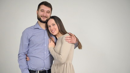 Happy young couple standing together on grey background
