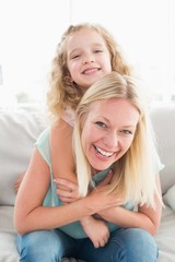 Happy mother piggybacking daughter on sofa