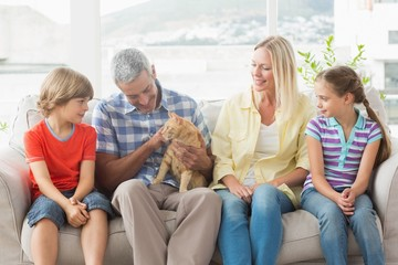 Family sitting with cat on sofa at home