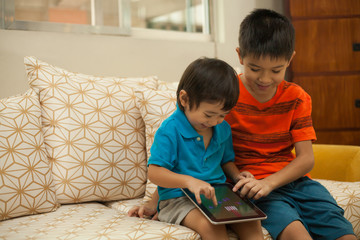 Two young boys playing with a digital tablet at home