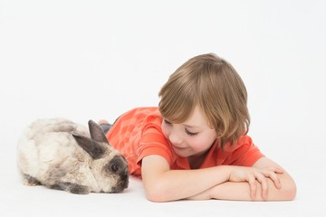 Cute boy lying down while looking at bunny