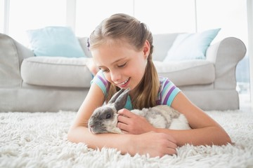 Girl playing with rabbit in living room