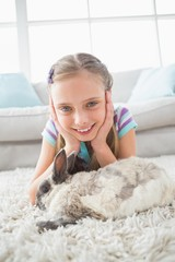Happy girl with rabbit lying on rug in living room