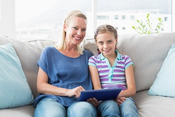 Happy mother and daughter using digital tablet on sofa