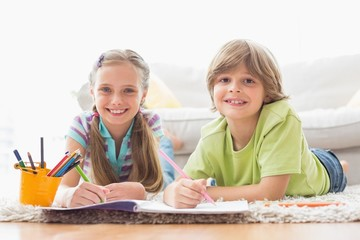 Portrait of happy siblings drawing while lying on rug